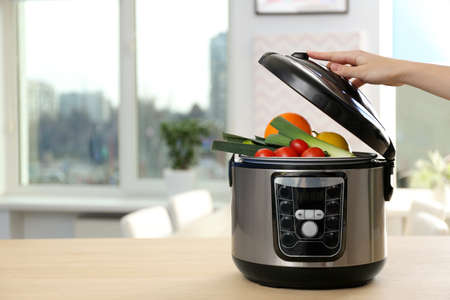 Young woman using modern multi cooker in kitchen, space for text