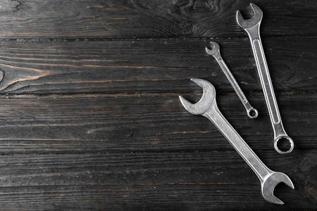 New wrenches on wooden background, top view with space for text. Plumber tools Standard-Bild
