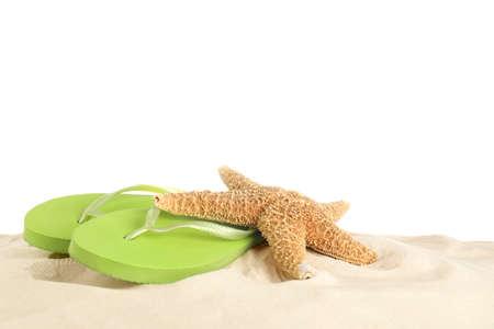 Chanclas y estrellas de mar en la arena contra el fondo blanco. Accesorios de playa Foto de archivo
