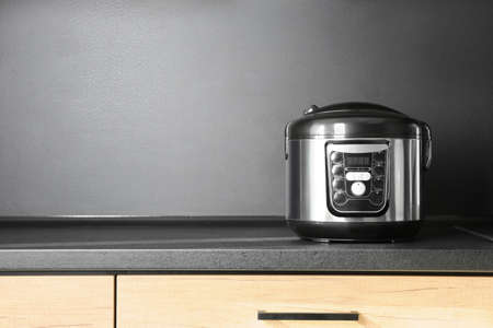 Modern multi cooker in kitchen, space for text. Domestic appliance
