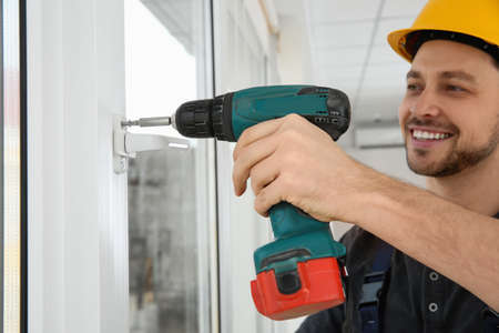 Construction worker using drill while installing window indoors Stock Photo