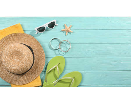 Flat lay composition with beach accessories on wooden background. Space for text