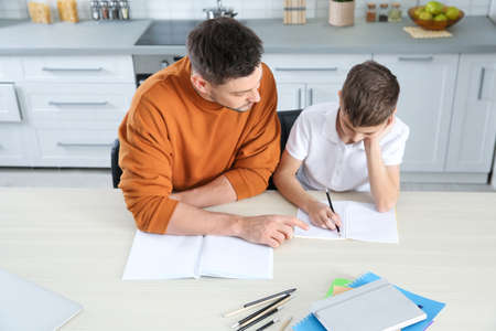 Dad helping his son with homework in kitchen, above view Imagens