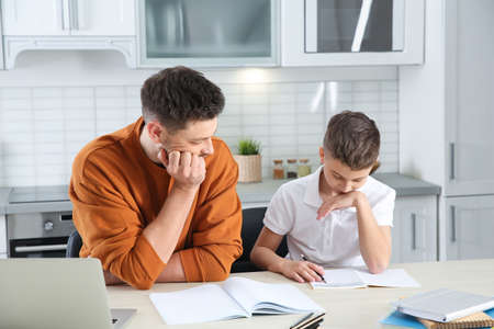 Dad helping his son with difficult homework assignment in kitchen