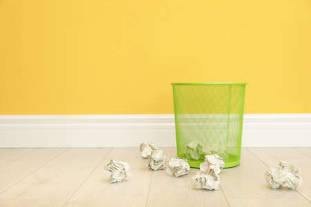 Metal bin and crumpled paper against color wall, space for text Stock Photo