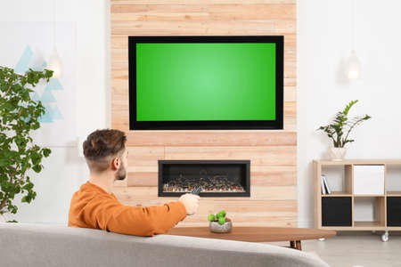 Man watching TV on sofa in living room with decorative fireplace