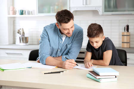 Dad helping his son with homework in kitchen