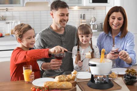 Happy family enjoying fondue dinner at home