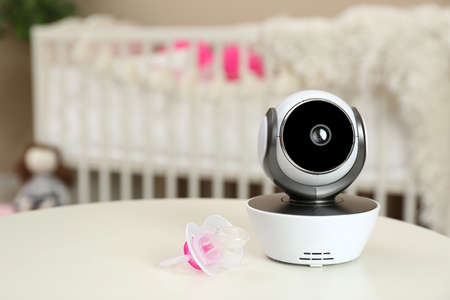 Modern CCTV security camera and pacifier on table in nursery. Space for text
