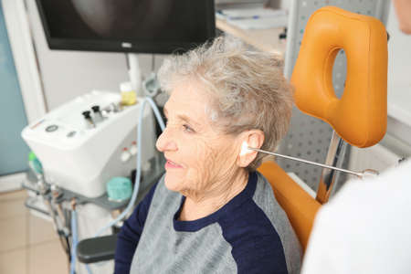Professional otolaryngologist examining senior woman with endoscope in clinic. Hearing disorder