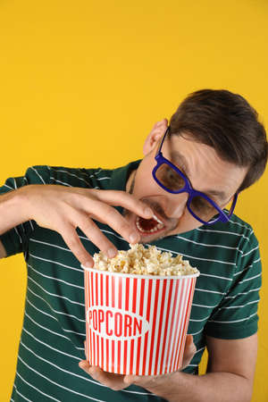 Man with 3D glasses eating tasty popcorn on color background