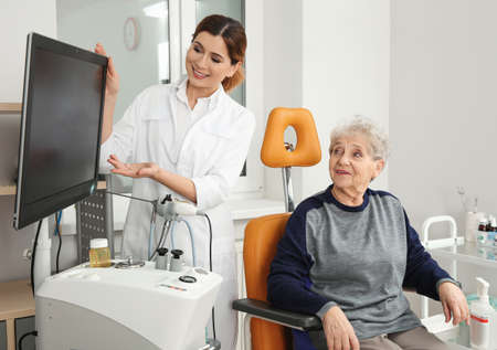 Senior woman visiting professional otolaryngologist in clinic. Hearing disorder