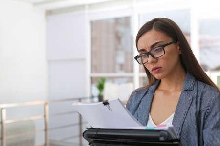 Junge Frau, die mit Dokumenten im Büro arbeitet. Platz für Text