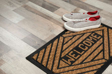 New clean doormat with word WELCOME and shoes on floor. Space for text Banco de Imagens