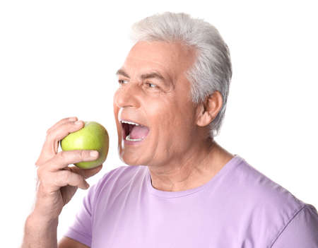 Mature man with healthy teeth and apple on white background Foto de archivo