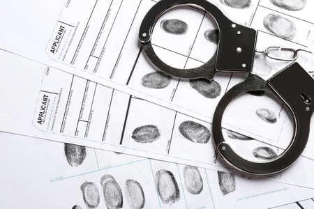 Handcuffs and fingerprint record sheets, top view. Criminal investigation Stock fotó - 118829542
