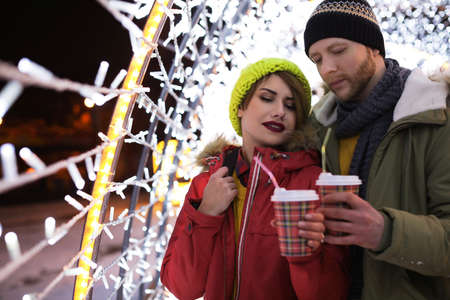 Young couple with cups of mulled wine at winter fair. Space for text