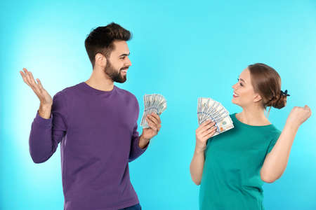 Happy young couple with money on color background