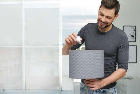 Man verandert gloeilamp in lamp binnenshuis Stockfoto