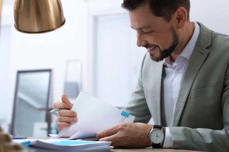 Geschäftsmann, der mit Dokumenten am Tisch im Büro arbeitet