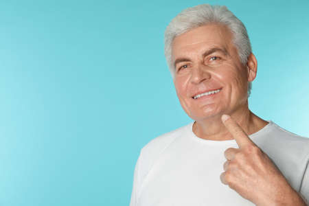 Mature man with healthy teeth on color background. Space for text