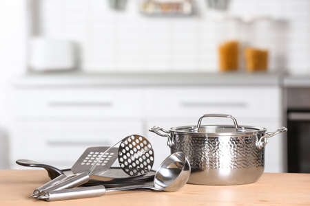 Set of clean cookware and utensils on table in kitchen. Space for text