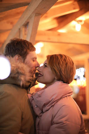 Cute couple in warm clothes at winter fair