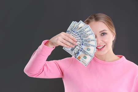 Portrait of happy young woman with money on grey background Standard-Bild - 120281403