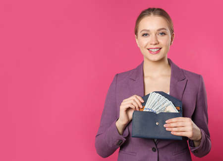 Happy young businesswoman with wallet full of money on color background. Space for text