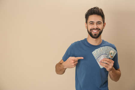 Portrait of happy young man with money on color background. Space for text Stock fotó