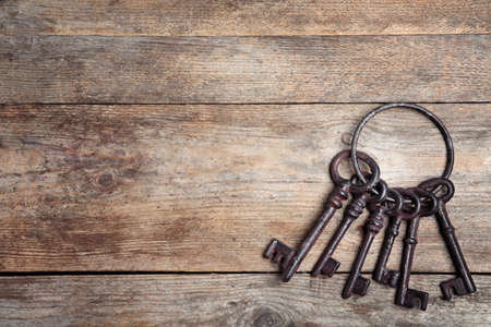 Bunch of old vintage keys on wooden background, top view with space for text