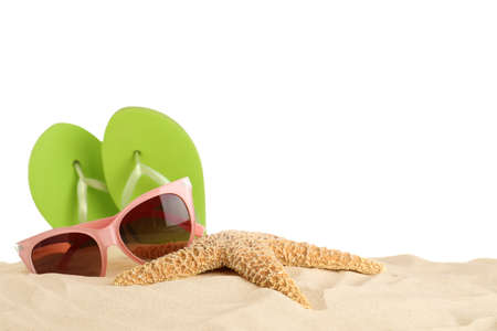 Beach accessories on sand against white background. Space for text
