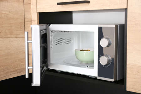 Open modern microwave oven with dish in kitchen
