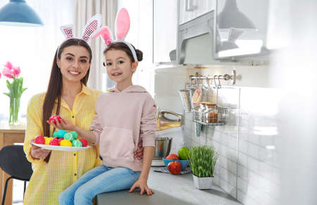 Mother and daughter with bunny ears headbands and painted Easter eggs in kitchen, space for text Stock Photo
