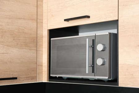 Modern microwave oven on shelf in kitchen Reklamní fotografie