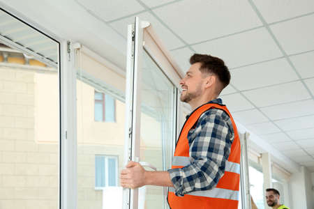 Construction worker installing plastic window in house Archivio Fotografico