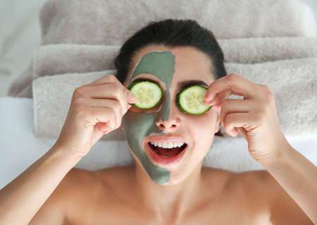 Pretty woman with clay mask on her face holding cucumber slices in spa salon, above view