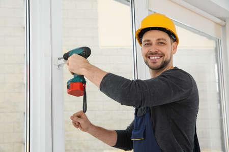 Trabajador de la construcción con taladro mientras instala la ventana en el interior