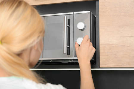 Young woman adjusting modern microwave oven in kitchen, closeup