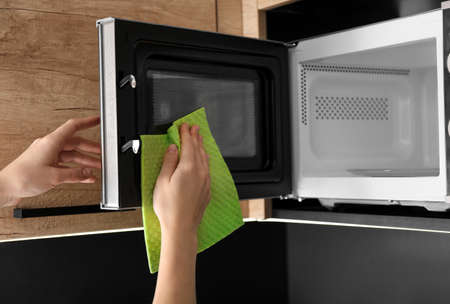Woman cleaning microwave oven with rag in kitchen, closeup