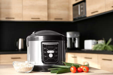 Modern multi cooker and ingredients on table in kitchen. Space for text 版權商用圖片