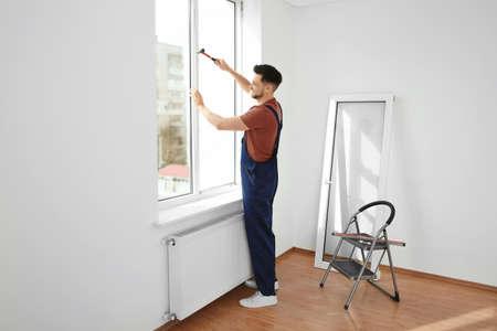 Professional construction worker installing plastic window indoors Stock Photo
