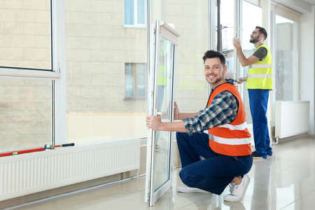 Construction workers installing plastic windows in house