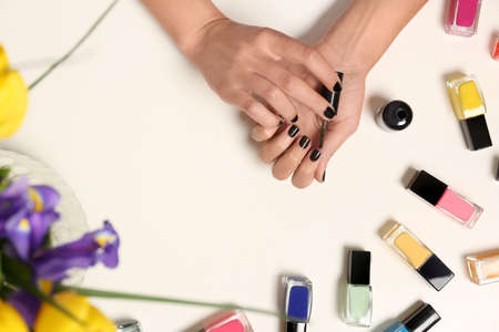 Woman applying nail polish near bottles on white table with flowers, top view Stock Photo