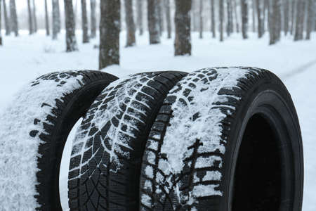 New winter tires covered with snow near forest, closeup Stockfoto