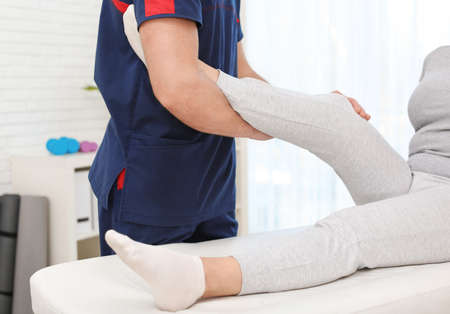 Physiotherapist working with patient in clinic, closeup. Rehabilitation therapy