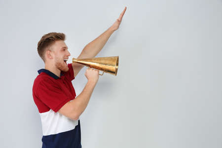 Young man with megaphone on light background. Space for text