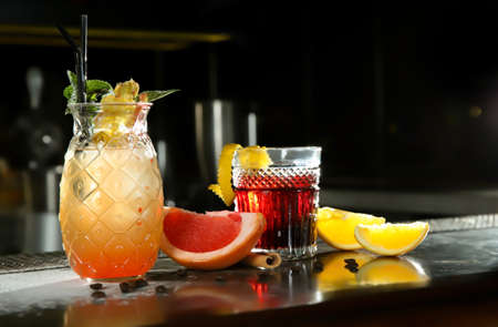 Fresh alcoholic cocktails in glasses on bar counter