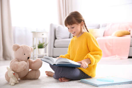 Cute little girl with teddy bear reading book on floor at home 写真素材