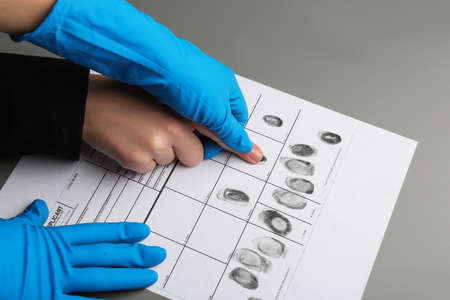 Investigator taking fingerprints of suspect at table, closeup. Criminal expertise Stock Photo